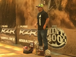 A winner poses with his prizes after the 2015 Polaris RZR Mint 400 awards banquet.